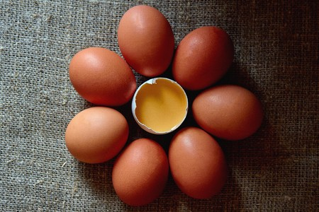 Fresh village chicken eggs lie on the surface of the table with a wooden spoon, one broke. Zdjęcie Seryjne