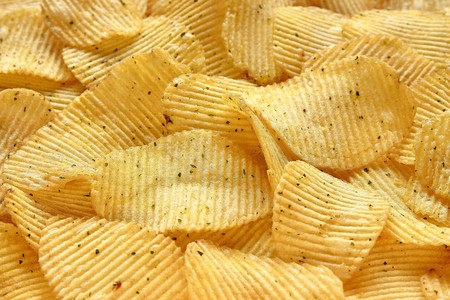 Textured background of natural corrugated potato chips