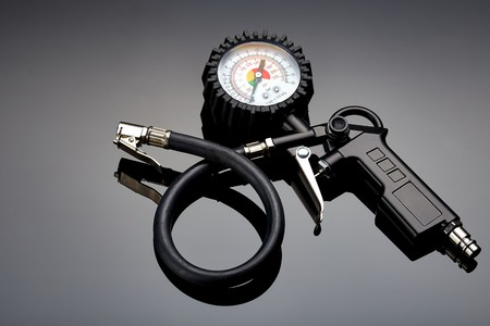 the pressure gauge of the compressor to control the pressure in the tires on a dark background closeup