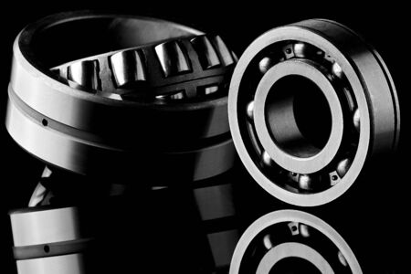 Close-up of a set of ball and roller bearings for repair lying on the desktop in the dark. Can be used as a background Imagens