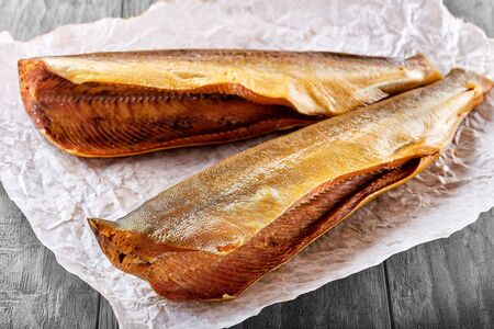 Fresh hot and cold smoked fish lies on a paper napkin on a wooden table
