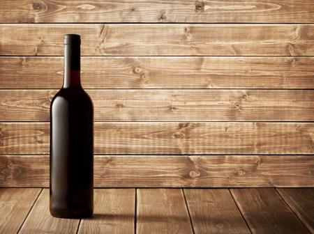 botella: Botella de vino rojo sobre un fondo de madera Foto de archivo