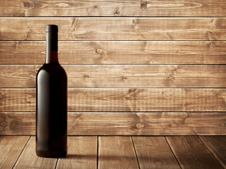 Red wine bottle on a wooden background Stock Photo