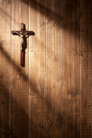 Suffering of Jesus Christ on the wooden wall. With shadows from a window frame. photo