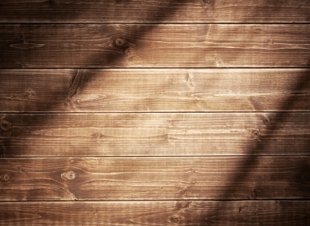 Wooden wall background in a evening light. With shadows from a window frame.