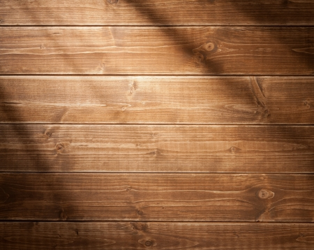 table: Wooden wall background in a morning light. With shadows from a window frame.