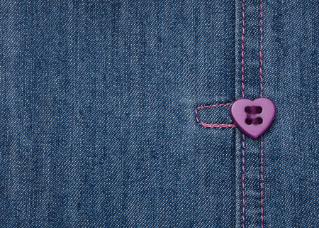 Purple heart shape button,sewed on a denim jeans cloth photo