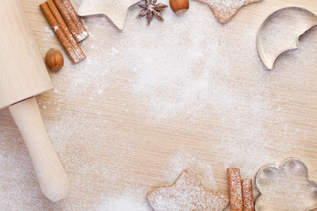 Baking christmas cookies- rolling pin,cookie cutters,cinnamon,anise, hazelnuts on wooden background photo