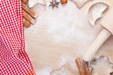 Baking christmas cookies- rolling pin,cookie cutters,cinnamon,anise, hazelnuts on wooden background Stock Photo - 24430505