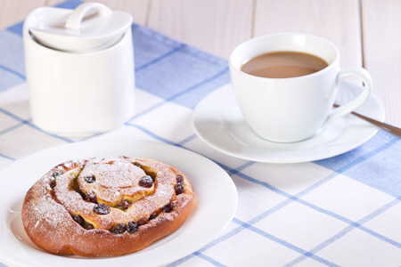 Sweet bun with raisins and coffee cup on wooden table