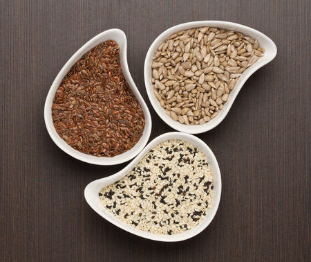 Sesame,flax and sunflower seeds in white bowl Stock Photo