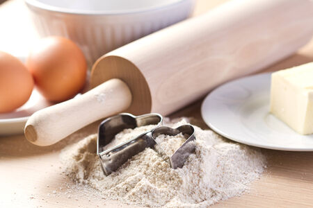 Ingredients for baking cookies and heart shaped cookies cutters photo