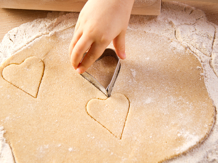 Kids hand with cookies cutter on cookies dough photo