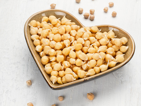 Chickpea sprout in heart shaped bowl on white wooden background photo