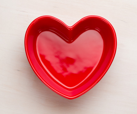 Red heart shaped bowl on white wooden surface