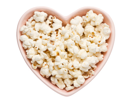 Fresh popcorn in heart shaped bowl isolated on white photo