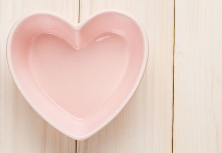 Heart shape bowl on white wooden table photo