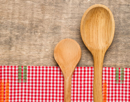 Wooden spoons and napkin on wooden surface photo