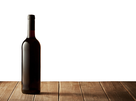 Red wine bottle on  wooden table isolated on white