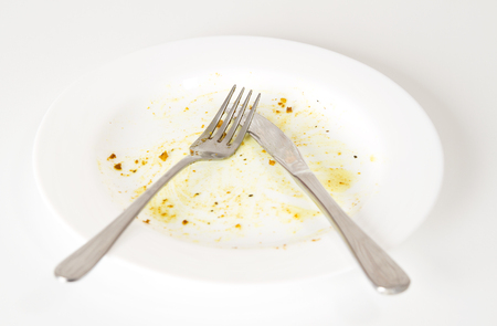Dirty white plate and knife and fork on white kitchen table photo