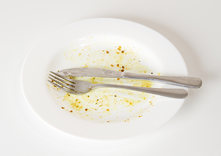 dirtiness: Dirty white plate and knife and fork on white kitchen table Stock Photo