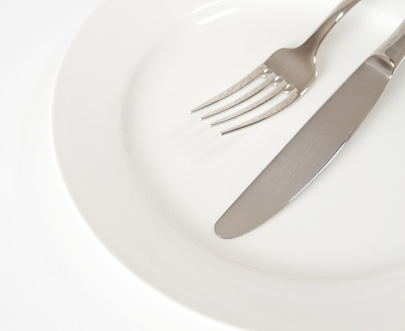 Cutlery on a plate on white kitchen table photo