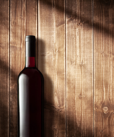 Red wine bottle on a wooden background photo