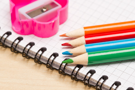 Colored pencils,notebook and pencils sharpener on table photo