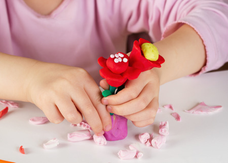 sculpt: Child hands playing with colorful clay