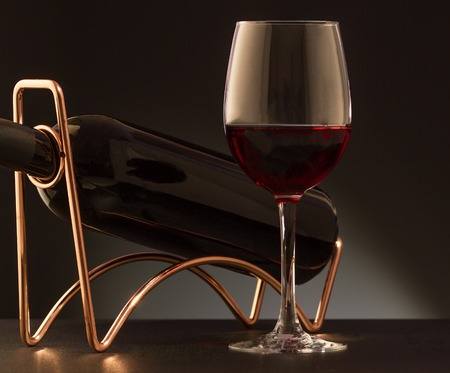 responsibly: Glass of red wine and red wine bottle  on a metal wine rack