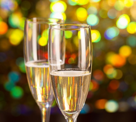 glass bottles: Pair glass of champagne and champagne bottle on bokeh background Stock Photo