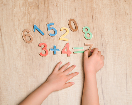 equation: Child hands with simple mathematical equation against wooden table Stock Photo