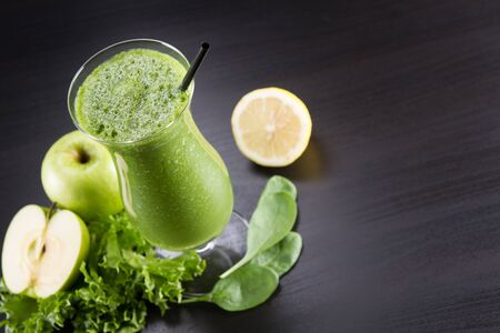 Glass of fresh cold smoothie with fresh fruit and spinach