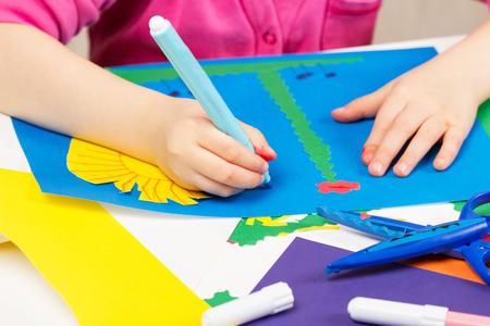 engrapadora: El niño hace la aplicación de papel de color