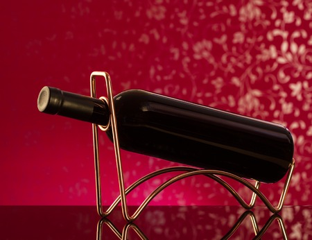 responsibly: Red wine bottle  on a metal wine rack