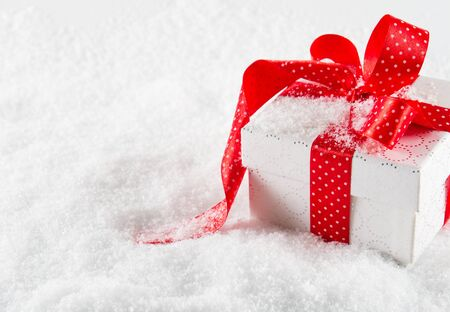 goodie: Gift box with red ribbon and bow on snow