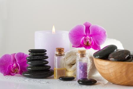Spa-Konzept. Steine, ätherisches Öl, Meersalz, Orchideenblüte, Kerze Standard-Bild - 83335415