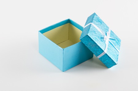 Empty blue gift box with ribbon on white