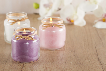 Burning purple, pink and white candles on wooden table
