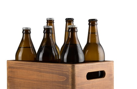 Craft beer bottles in wooden box isolated on white background Stock Photo