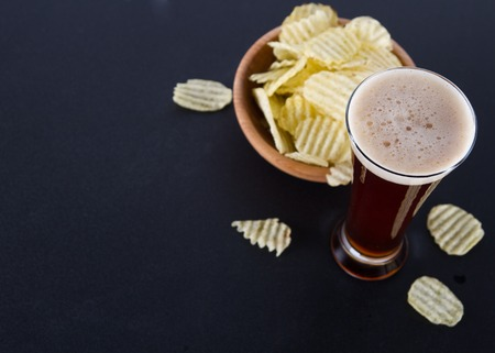 Dark beer and potato chips on black table
