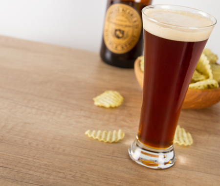Dark beer and potato chips on wooden table