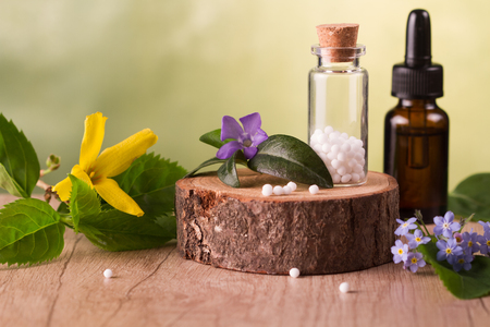 Bottle of homeopathic globules,homeopathic remedies and flowers