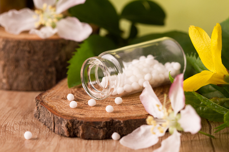 Bottle of homeopathic globules and flowers