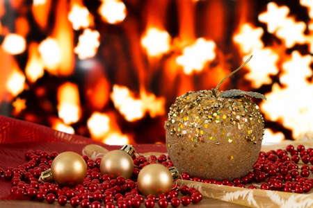 Christmas balls and golden beads on a blurred background. Stars and garlands. Golden apple handmade.