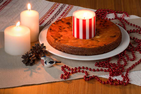 fairy cakes: Handmade Pie with candles on the wooden table. Christmas treats. Christmas mood. Fairy cakes with a magic light from the candles. Stock Photo