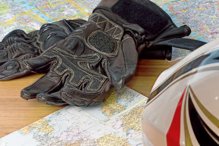 Motorcycle helmet, gloves, and road maps on a wooden table. Journey Dream. Travel route.