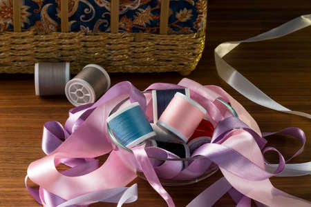 sewing box: Composition of colorful ribbons and thread on a wooden table. Materials for sewing.