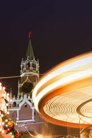 carnival ride: Christmas lighting in Moscow. Fair on the Red Square. Festivities. Christmas tree. Twisting carousel. A long exposure of a carnival ride. The Spasskaya Tower. Stock Photo