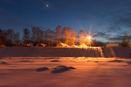 Winter evening in the Russian village. Veliky Ustyug, Russia. View from the frozen river Sukhona. Travel to the North of Russia. Stock Photo